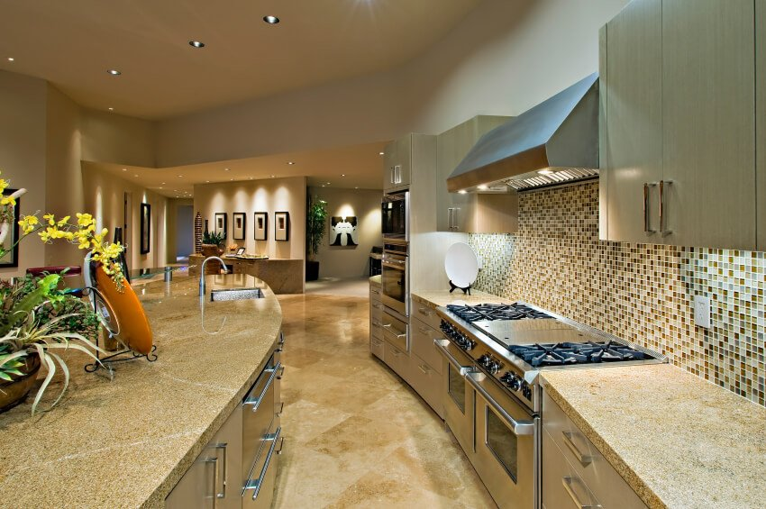 A slightly curved kitchen with a bold glass mosaic tile backsplash and light granite countertops.