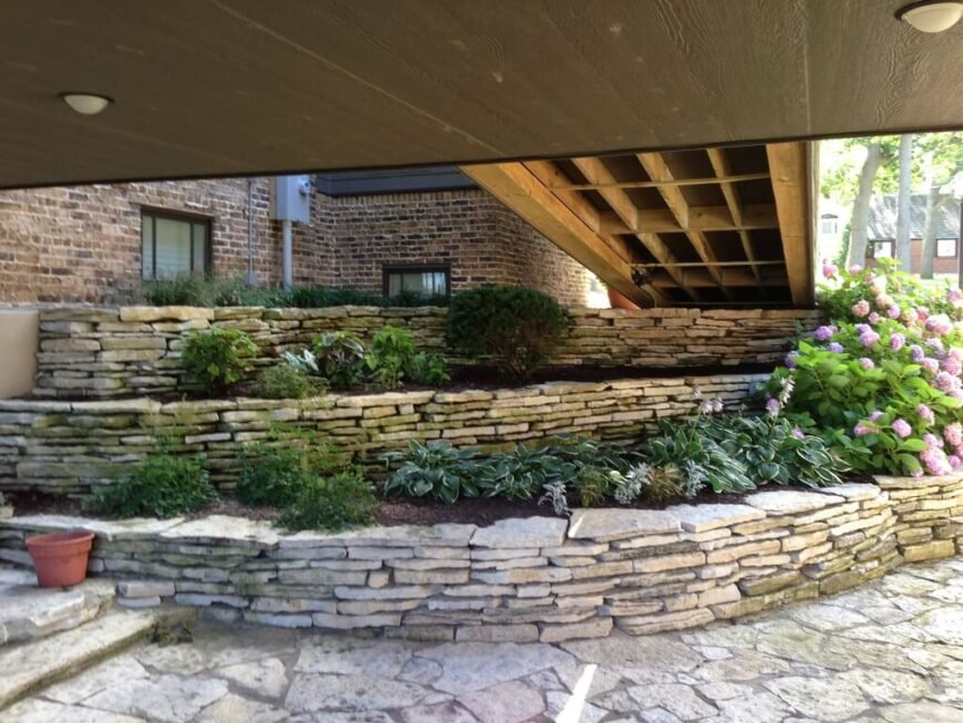 A series of layered stone terraces between the highest and lowest levels of a split-level home. A ramp is overhead.