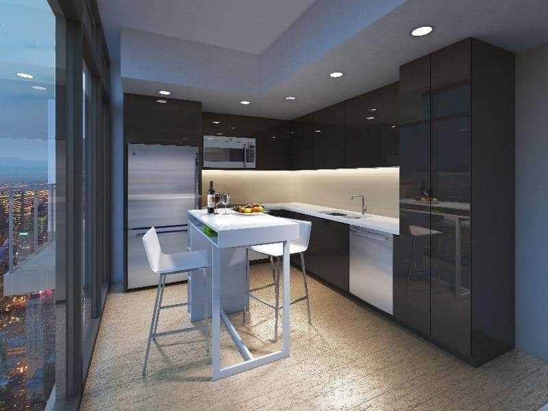 An apartment kitchen with glossy black cabinetry and white countertops. The island has shelving on one side beneath the countertop.