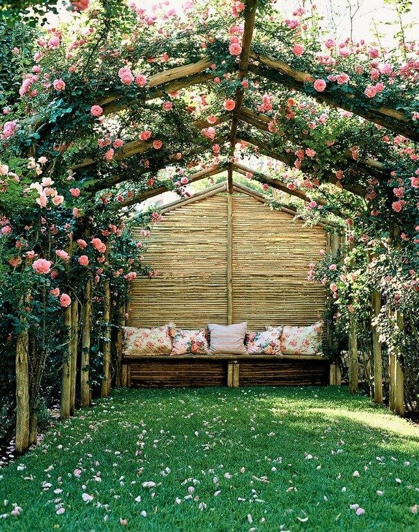 A natural wood trellis, bedecked in climbing roses, creates the perfect space for an afternoon nap.