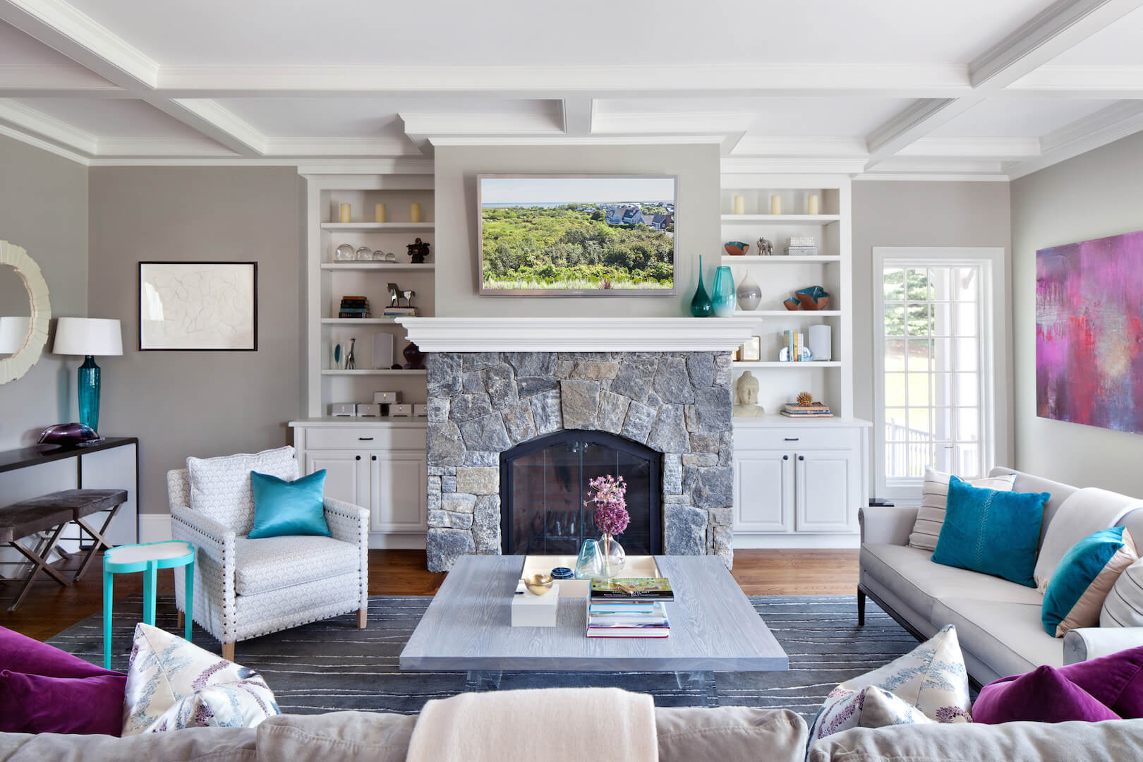 Another shot of the living room featuring the stone fireplace and built-in bookcases on either side of the fireplace. The striped dusky blue rug beneath the periwinkle coffee table contrasts nicely with the other shades of blue in this living room.