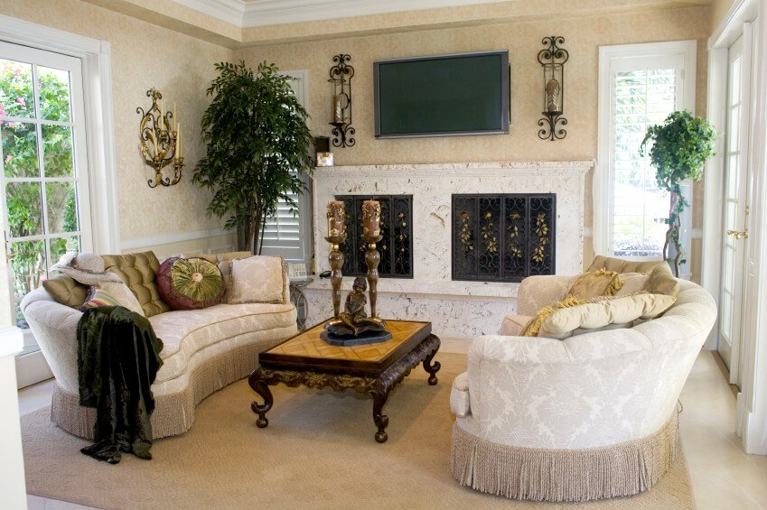 An elegant, traditional style small living room with matching curved sofas and an ornate coffee table with a light wood inlay. The enormous fireplace has two wrought iron screens surrounded by white marble. A wall-mounted television rests above the mantle. French doors to the right behind one of the sofas lead out into the backyard.