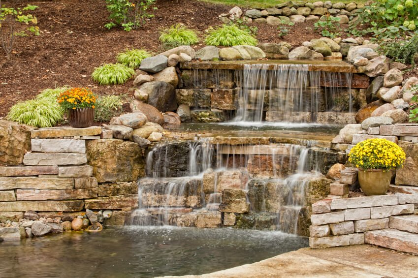 A deep pond at the bottom of a hill covered in cedar wood chips. A stone waterfall cascades down the hill into the pool. Stone steps lead up to the right.