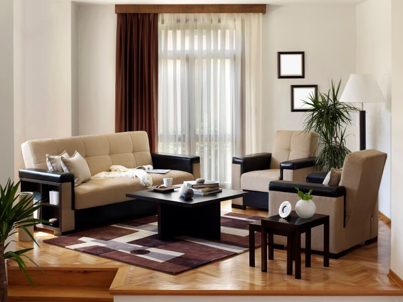 A small living room arrangement on a wood floor in a chevron pattern. The space is raised from the main floor via a few steps and is host to modern furniture in black and beige. The burgundy area rug adds a pop of color that ties in the drapes. The oddly shaped room is a perfect dedicated visiting area near the front door. The sides of the sofa also double as storage.