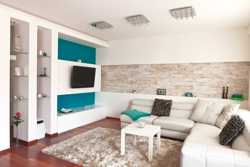 A contemporary living room with a strip of stone tile inset as a shelf into the wall behind the sectional. The room is lit by three small glass light fixtures. Perhaps the most eye-catching feature of this room is the bold turquoise accent wall behind the white television stand. Elements like a single glass vase with a rose and animal print pillows add personality and charm to the space.