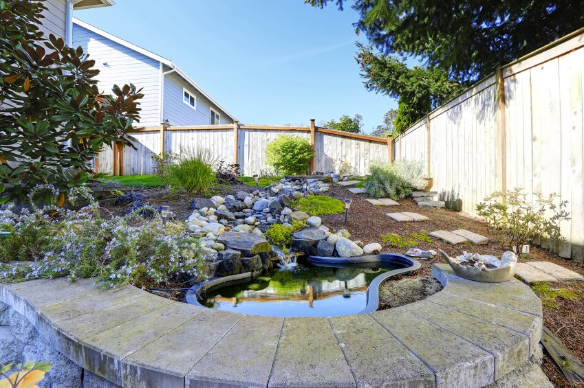 A small garden pool with a stream emptying into the pond. A short wall of stone blocks overlooks the pond.