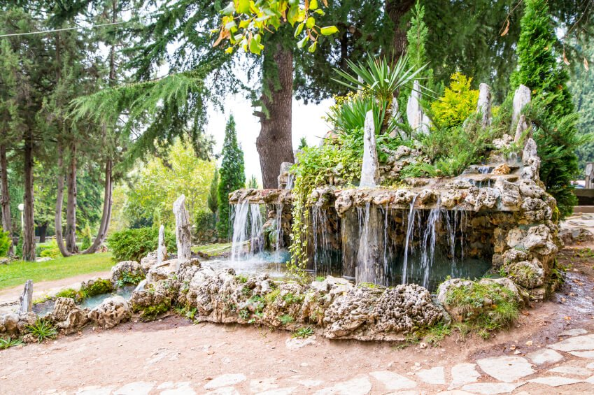 A beautiful garden pond surrounded by porous stones and moss. A high stone ledge above the pond has cascading water, creating wonderful ambiance.