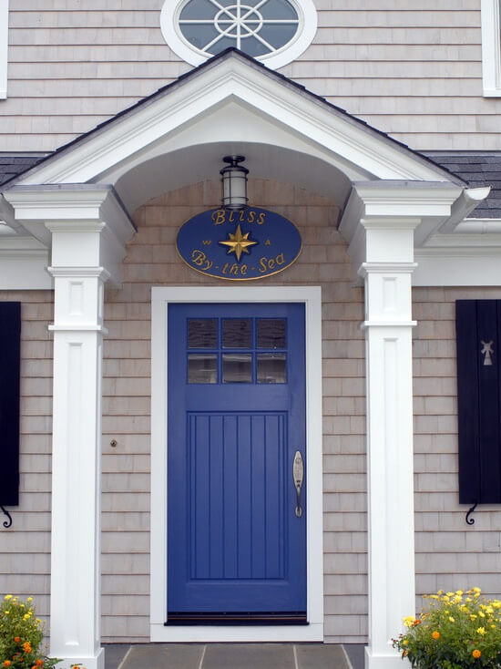 """This house has a white stoop roof which is supported by two rectangular pillars. Hanging in the ceiling of the roof is a door lamp. It has a blue front door with glass window panels. The door has a nickel door lock and handle. It also has a white door frame. Just above the door there is a round blue sign which says: """"Bliss By the Sea."""""""