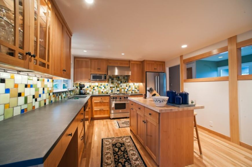 A wood kitchen with a bold, colorful, and somewhat zany backsplash in ceramic multi-colored tiles of varying sizes.