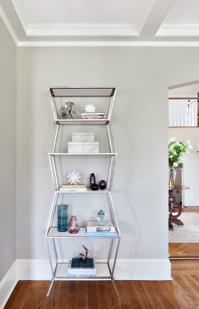 A close up of the modern shelving unit near the entrance to the room, which holds books and other eclectic decorative elements.