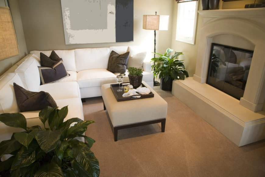 A small, carpeted living room with a raised hearth enclosed fireplace and several leafy houseplants. The upholstered ottoman has a tray that converts it into a coffee table. The white sectional is positioned to take full advantage of the wall space. The nook is a cozy, intimate spot to visit or enjoy the fireplace.