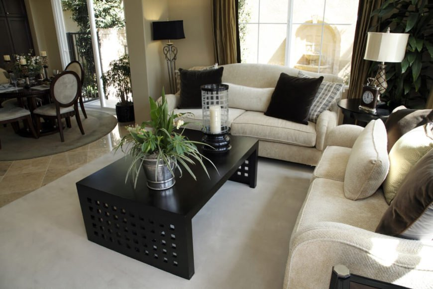 A living room that faces outward to the dining room. Tucked in a nook, the two loveseats and the glossy, dark wood coffee table are in a carpeted section of the home that gives way to tile in the dining room. Windows behind the sofas keep the space nice and bright. Accents include a tall candle holder, houseplants, and a small clock.