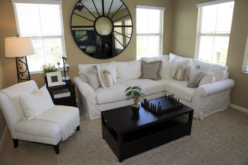 A mirror shaped like a wagon wheel hangs above part of the slipcovered sofa. The dark side table and coffee table provide stunning contrast to the taupe walls, carpet, and natural fiber area rug, in addition to the sharper contrast with the white sofa and chair. The lamp on the left has a wrought iron base with a vine pattern.