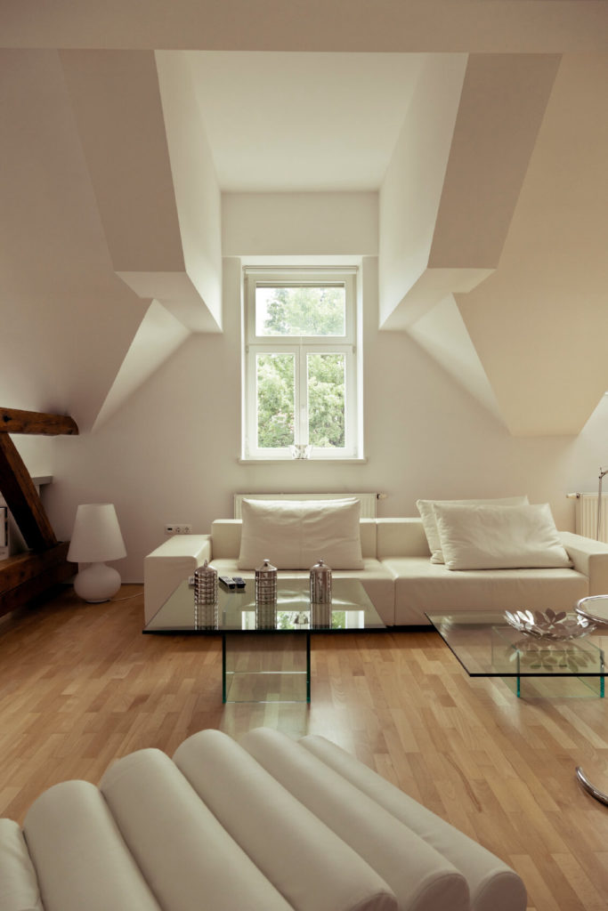 Attics are known for having somewhat awkward shaped ceilings, and this one is no exception. The space has been converted into a luxurious minimalist living room in white with a pair of glass coffee tables.