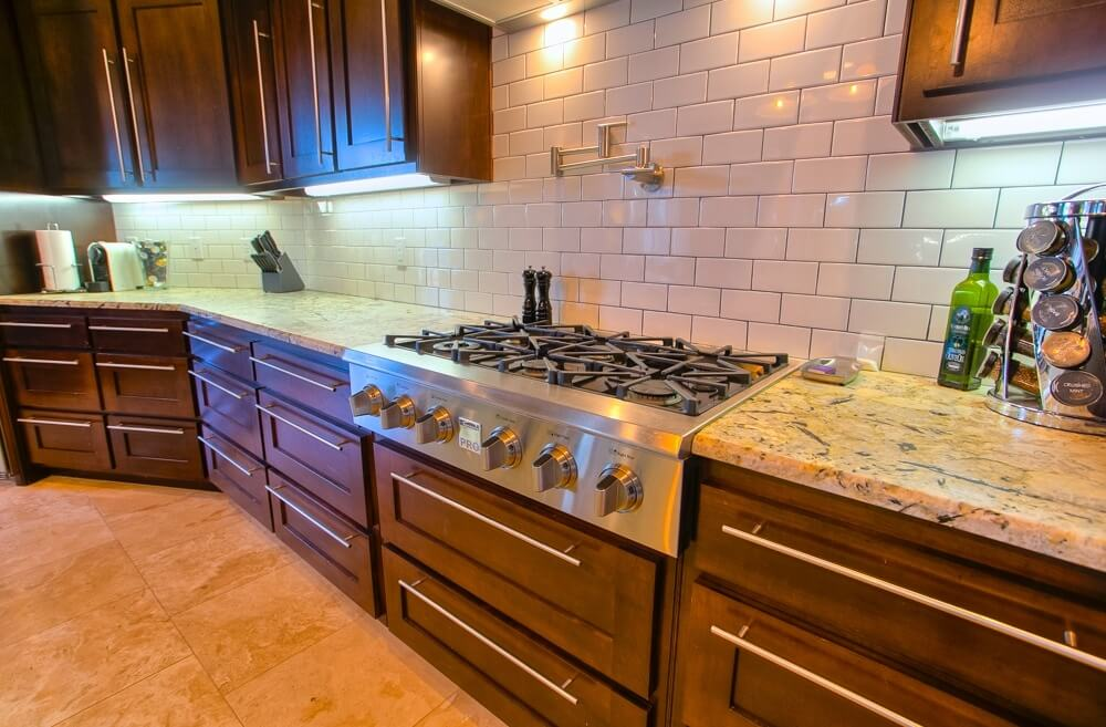 A contemporary kitchen with high end appliances and a beautiful white subway tile backsplash with a light grout.