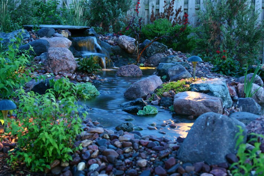 A stream-like pond with a small waterfall, edged by small stones and larger boulders. Small mushroom-shaped lights add unique ambiance at night. Small leafy plants, ground cover, and taller bushes surround the water feature.