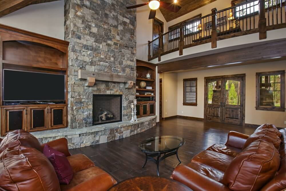 A view of the grand room from another angle, showing the open hearth of the fireplace, the double doors leading to the covered front entryway, and the open hallway on the second floor. The main light fixture in this room is a large ceiling fan. The bookcase on the left acts as a large entertainment center with additional storage on the top.