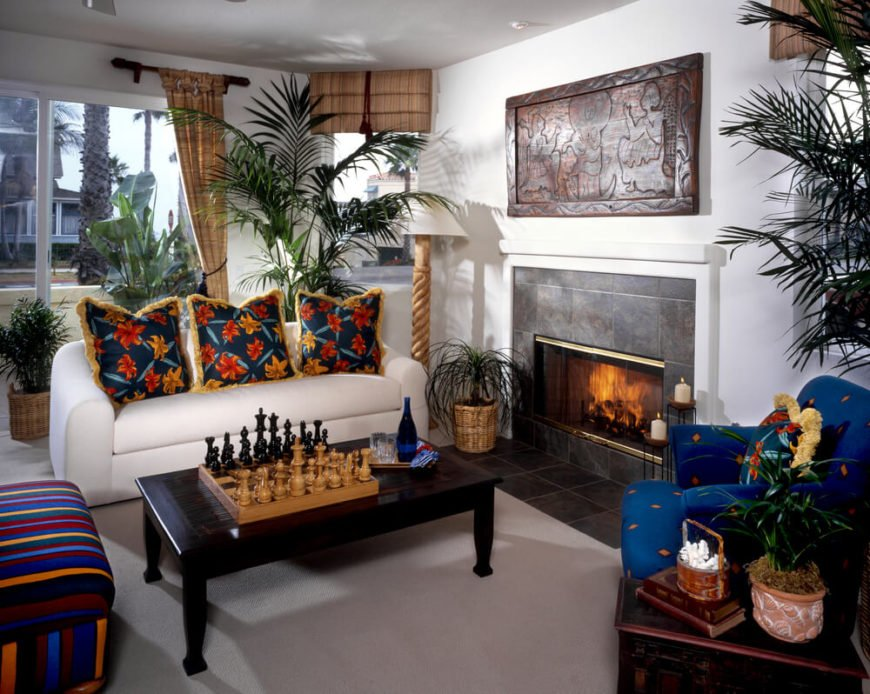 A bold, tropical-style living room with a striped armless chair, a blue armchair, and a white sofa with fringed hibiscus pillows. The small mantle above the tile, glass enclosed fireplace is topped by a mahogany carving. Accents include pottery, shells, carved lamps, and a large chess set.