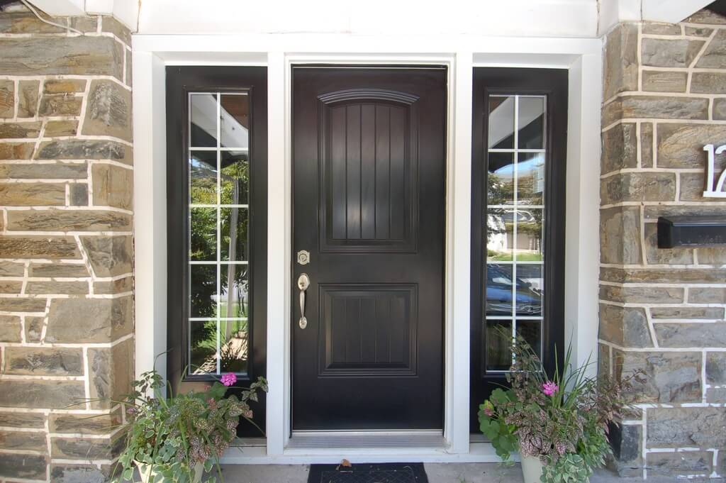 Large paned windows frame a matte black door with simple hardware on this stone brick home.