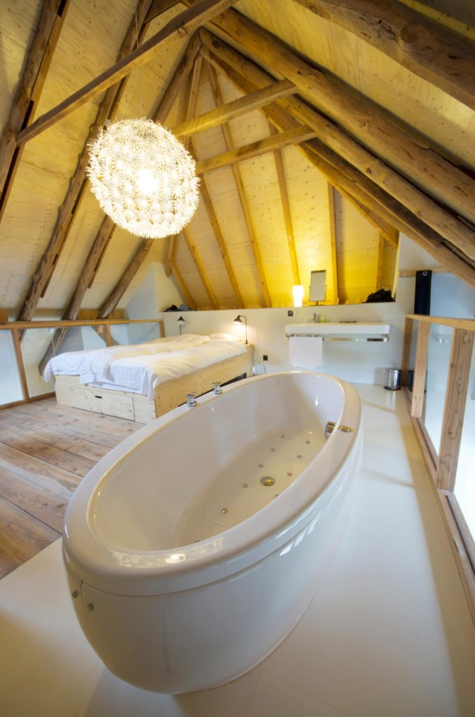 An attic bedroom and bathroom combined. Half the space is in a rustic wood, while the bathroom half is in a pristine white tile.