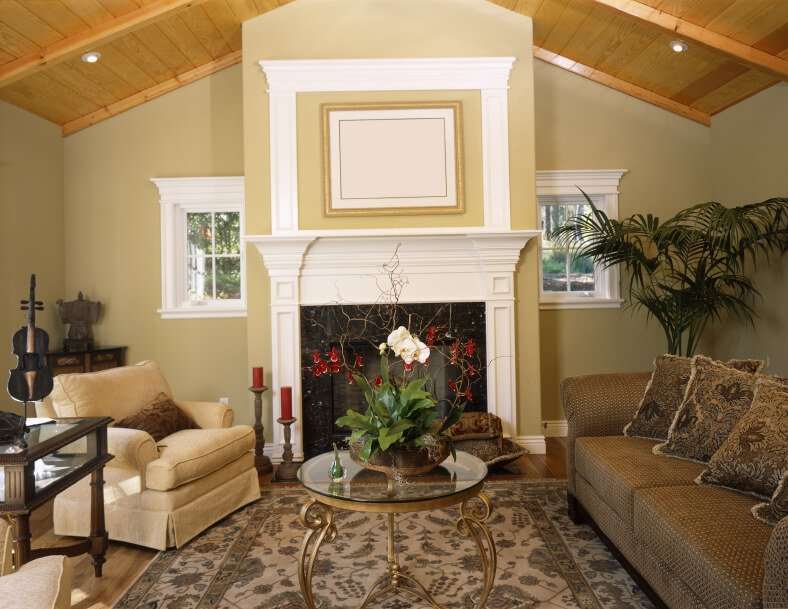A small living room with an elegant gilded glass-top coffee table and small windows flanking the white mantle enclosed fireplace. The gilded legs of the coffee table bow outwards, adding elegance to the traditional space. Exotic accents include a Japanese statue and an antique viola.