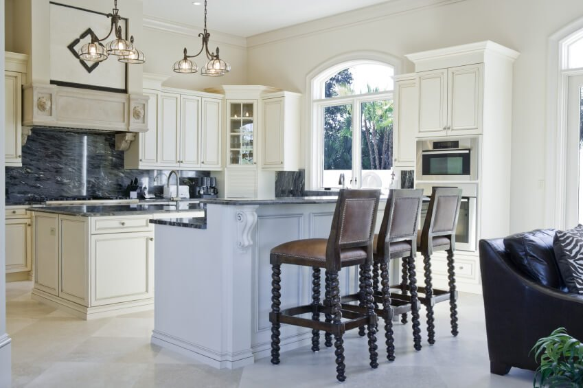 A pristine white and cream open-concept kitchen with a two-tiered second island that doubles as an eat-in bar. The backsplash is a gorgeous soapstone with lots of light gray veining.