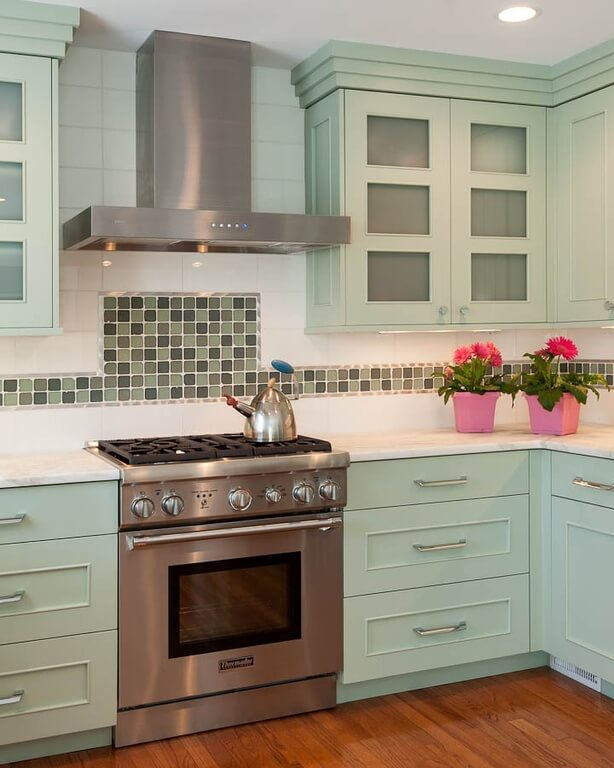 A simple, sweet country kitchen with mint cabinetry and an alternating pattern of green tiles along the white tile backsplash.