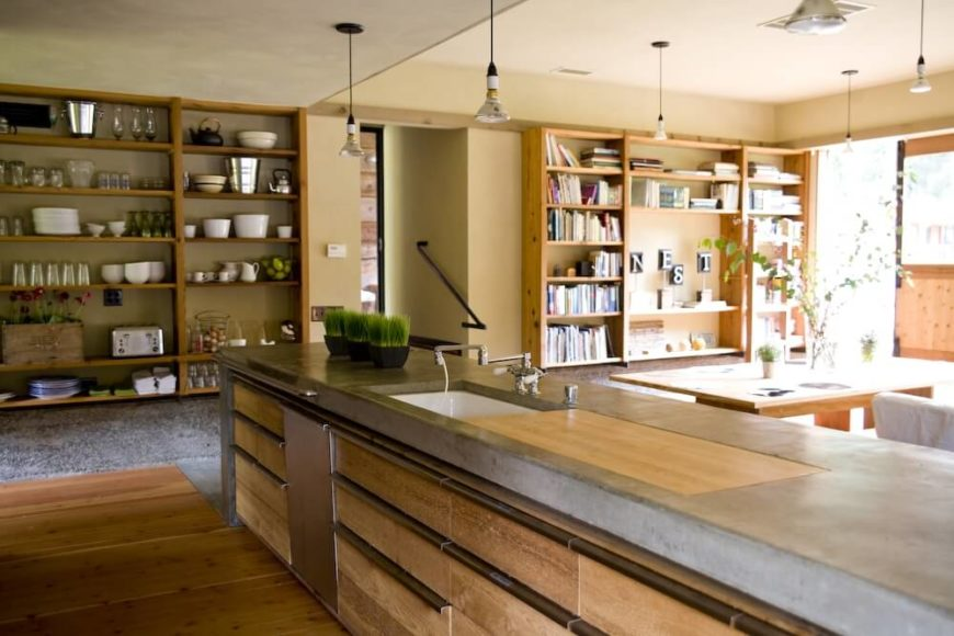 A view of the open concept living area from behind the kitchen island. Next to the sink is a section of butcher block in the otherwise concrete countertops. The rest of the room has built in shelving.
