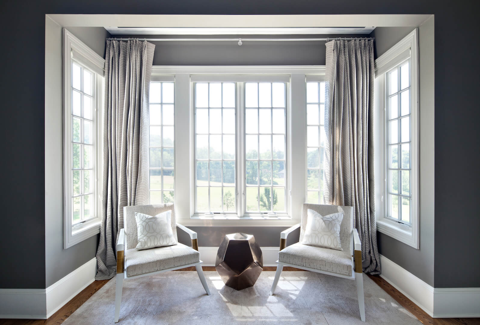 A small sitting area by the bay windows of the primary suite. The contemporary chairs are matched with a small area rug and a metallic side table in bronze. The subtle striped curtains behind the seating area add a dimension of pattern.