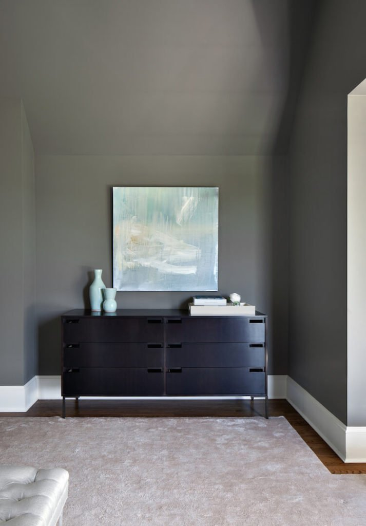 A small nook on the right side of the room is host to a modern-style dresser in a darker wood. The mint from the bed pillows is complemented by the mint pottery on the dresser and the soft water color painting above the dresser.
