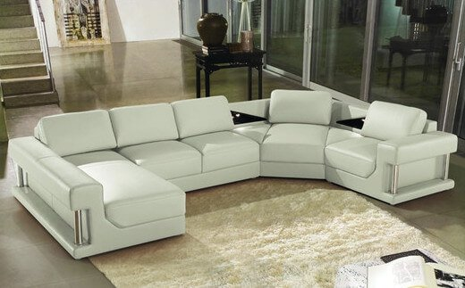 A lovely four piece sectional in white leather. The sides of the sofa have metal rods on either end, giving this otherwise plain sofa a bit of style. The corner seat has two triangular cushions on either side.