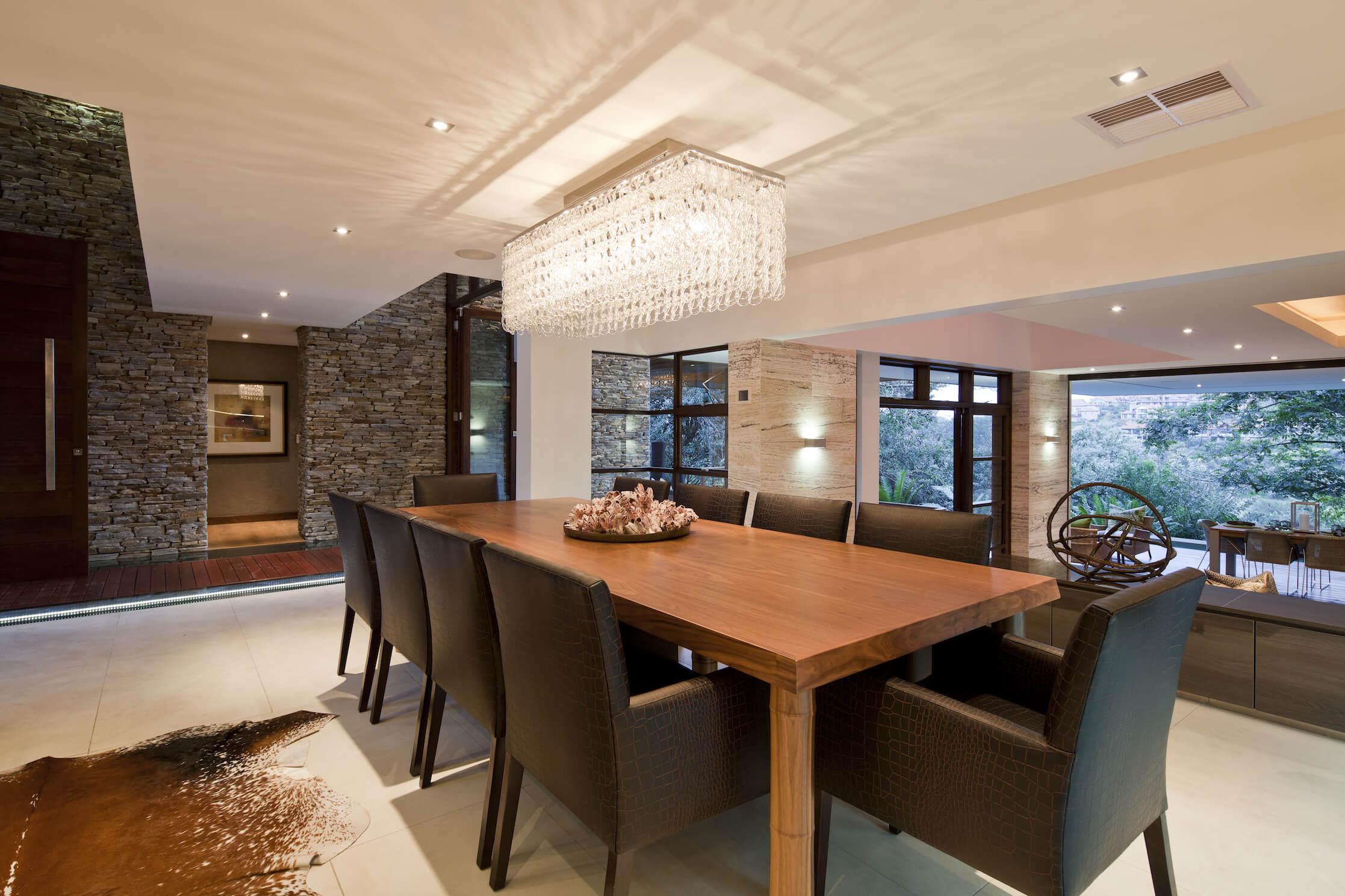 The formal dining room shares the open space with the kitchen, centered on a large natural wood dining table and chocolate toned dining chairs. A large shimmering box chandelier hangs above.