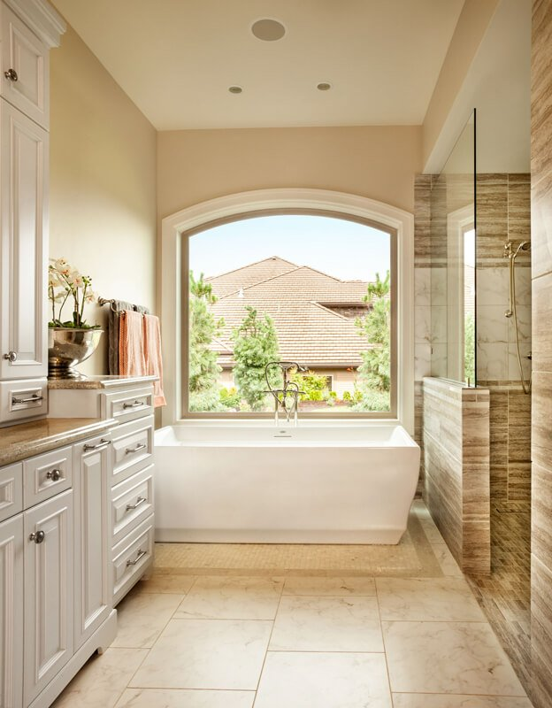The on-suite bathroom has a fantastic, deep soaking tub with high-end fixtures. To the right is the shower stall in striped brown stone tiles.