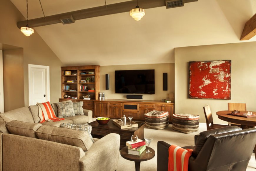 The rec room has a linen sectional and a faux leather recliner in chocolate brown. It also includes a large built-in entertainment center and a small game table.