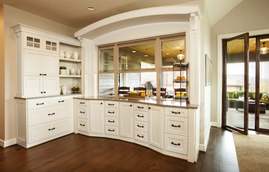 The opposite side of the kitchen, featuring an additional workspace and a passthrough to the family room. French doors open into the kitchen from the family room as well.