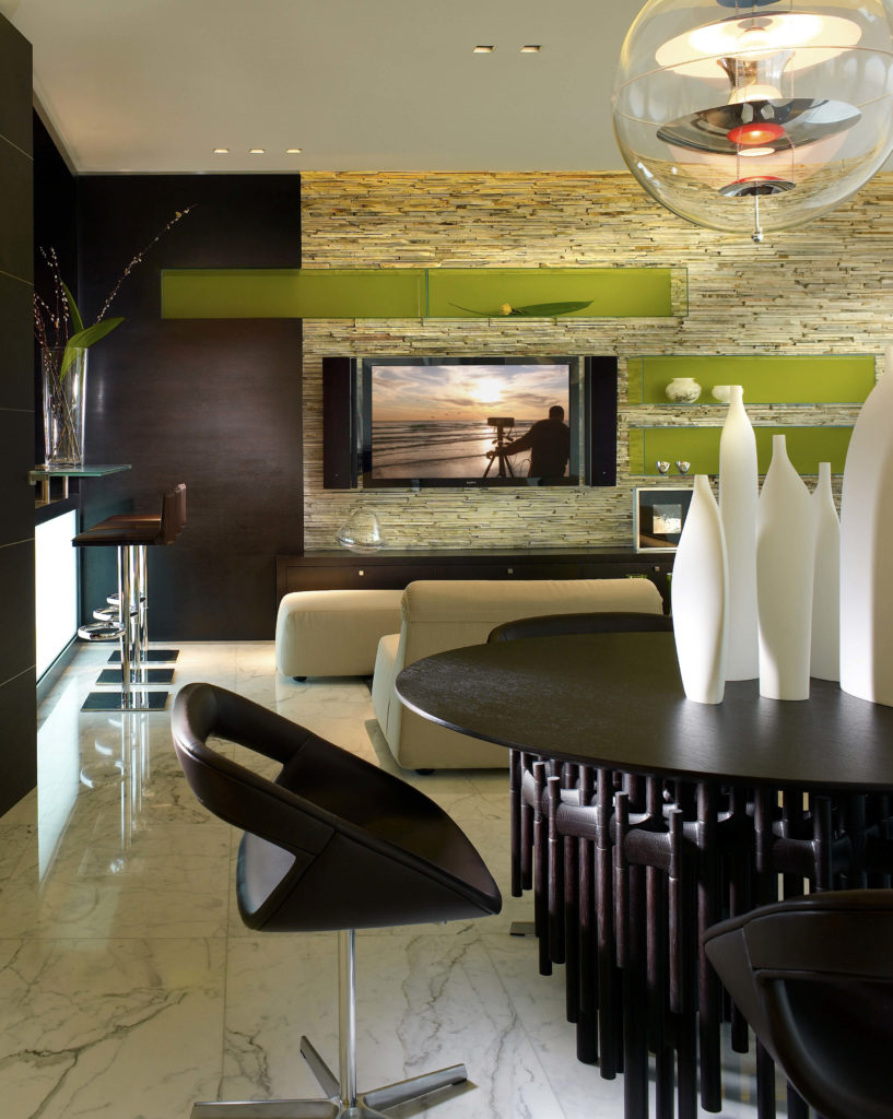 The bold semi-transparent green floating shelves, paired with the very modern light fixture over the small dining area makes for a casual family room for entertaining smaller groups. On the left there is a wet bar.