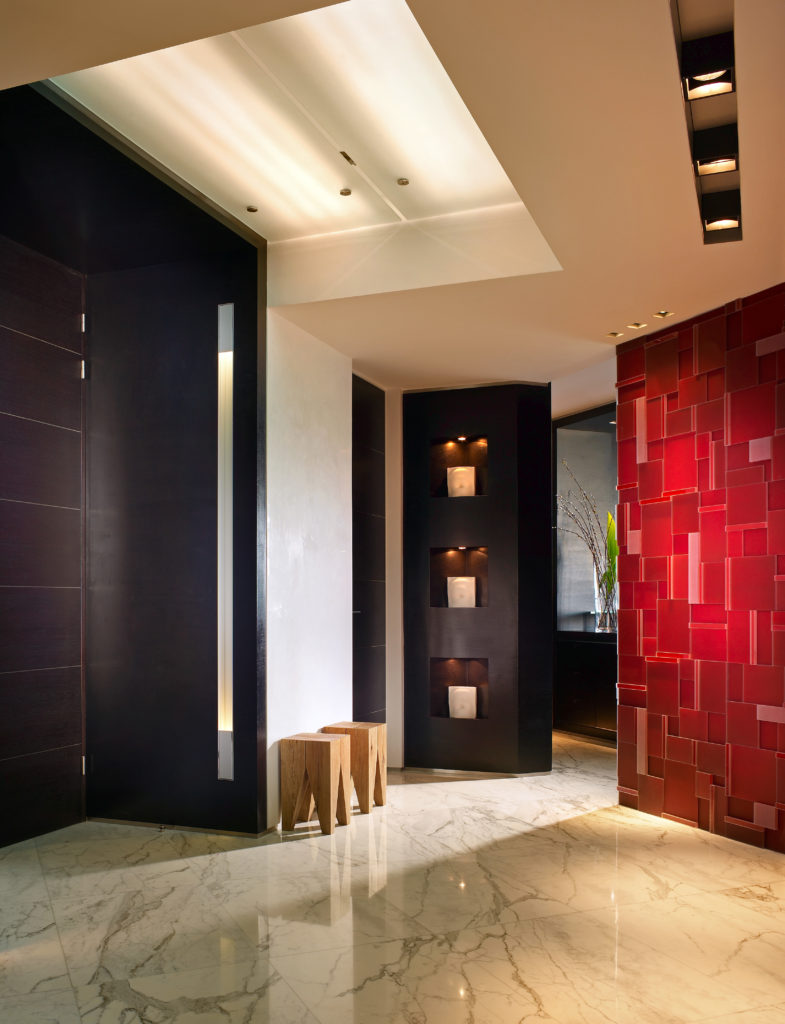 The entryway of the home has clothespin shaped wooden stools beside the door and another red polygon accent wall. Another wall has small lighted alcoves.