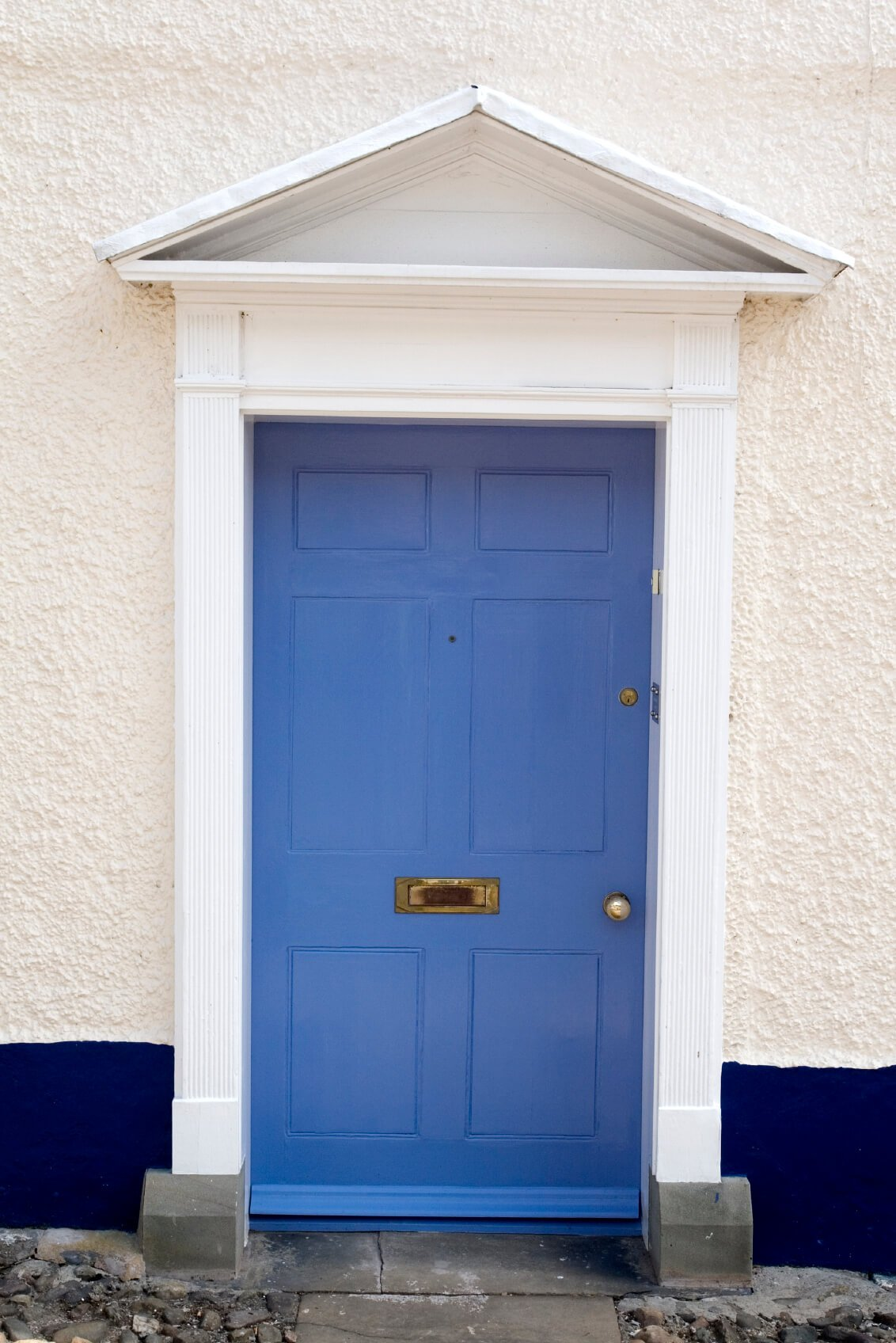 A blue front door situated on a front exterior wall of concrete which is painted white and navy blue.