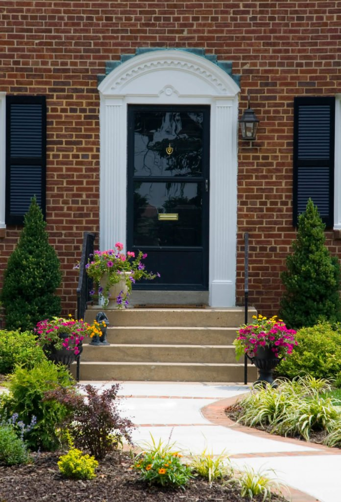 This traditional door with brass mail slot and shield knocker sits behind a glass panel storm door, flanked by a pair of white columns.