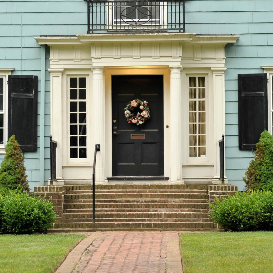 Home with a dark blue door atop brick steps flanked by cream columns and door frame. A cheery floral wreath bedecks the door.