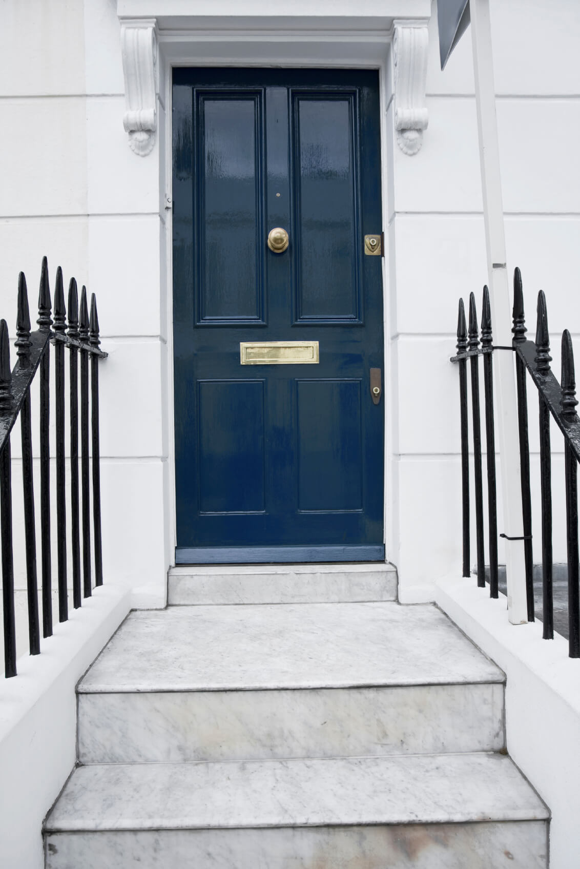 A white concrete front exterior with a blue front door. The front door features a brass door knob placed right in the middle. The door also features a peephole right above the door knob, two door locks, and a mail slot below. Right in front of the doorway are big white marbled steps and black steel fences.