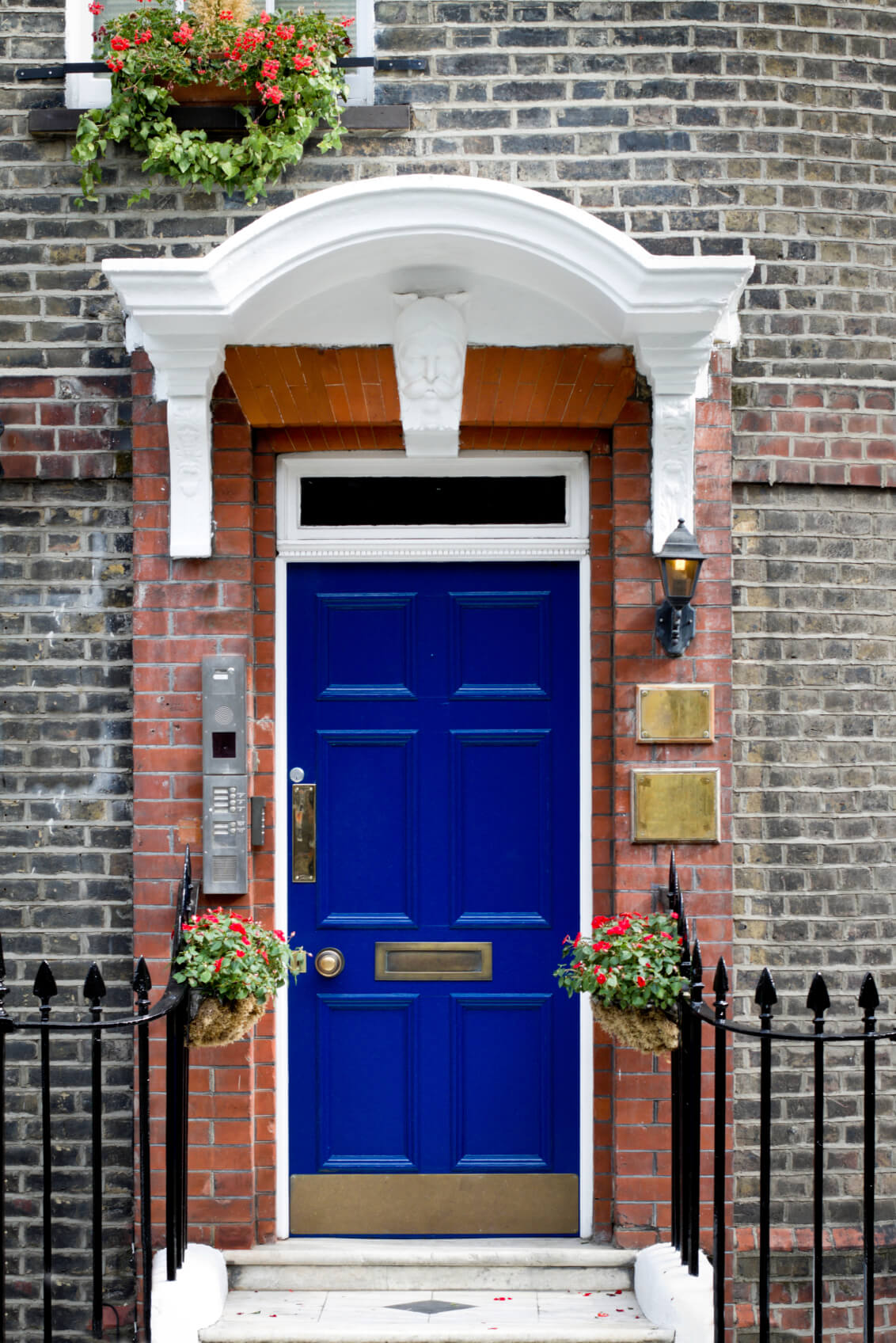 The facade of this home is made out of red brick. The doorway has red brick molding as well, with a white Roman style arch above it. It has a royal blue front door. The front door features a brass knob, door handle, a mail slot, a lock, a peephole, and a kick plate below. Also installed by the door is a door lamp, an intercom entry system, and two empty brass plates attached on the brick molding. It has a concrete doorstep with black steel fences and a couple of hanging plants.