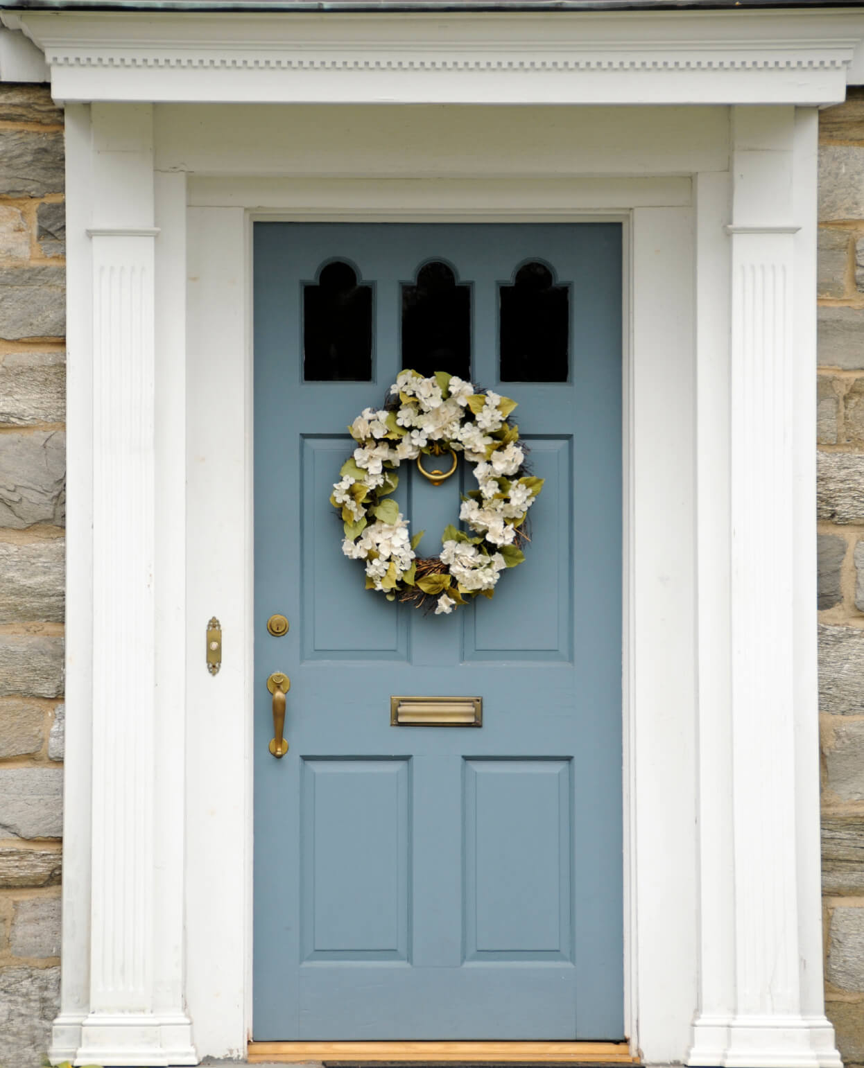 This house has stone front exterior. It has a light teal blue colored front door which has a series of glass panels. The front door has a brass lock, door handle, mail slot, and door knocker. Hanging above the brass door knocker is a wreath with white flowers. The front door also has a white door casing with a brass plated doorbell.