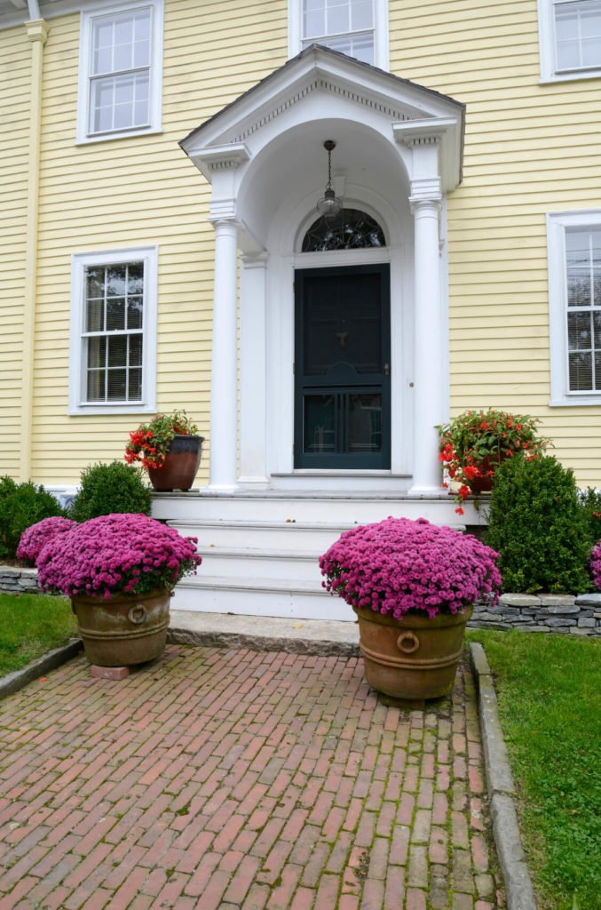 The vaulted white portico here frames a black front door, bookended by a pair of columns.