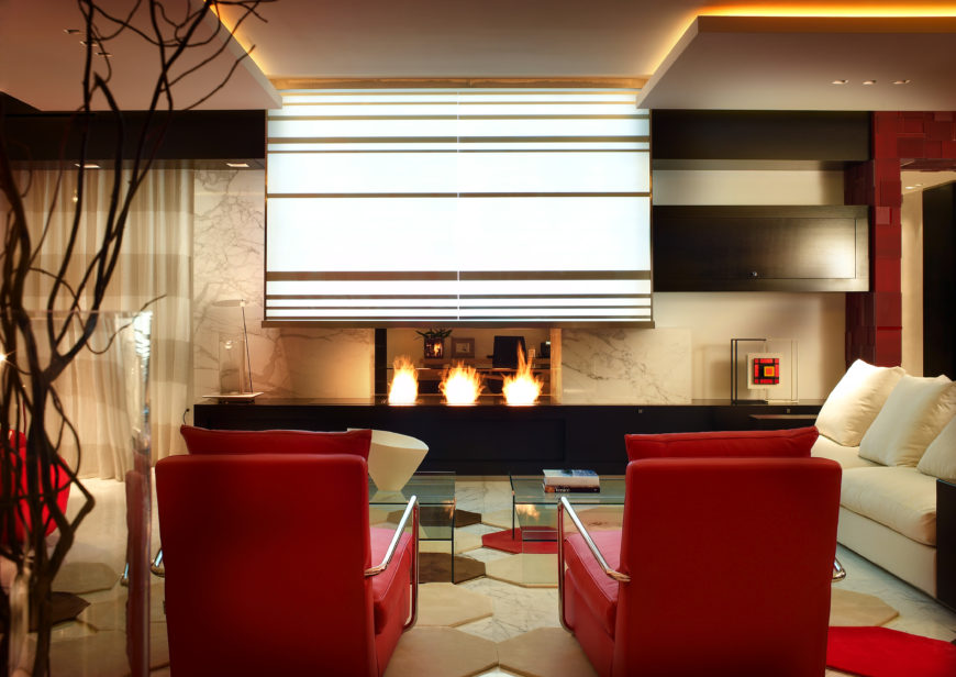 On the other side of the living room, another seating arrangement sits in front of a pass-through fireplace, through which you can see the home office. Three distinct flames make up the fireplace, with a large, lighted vent above it. The connected hexagonal rug continues throughout the space.