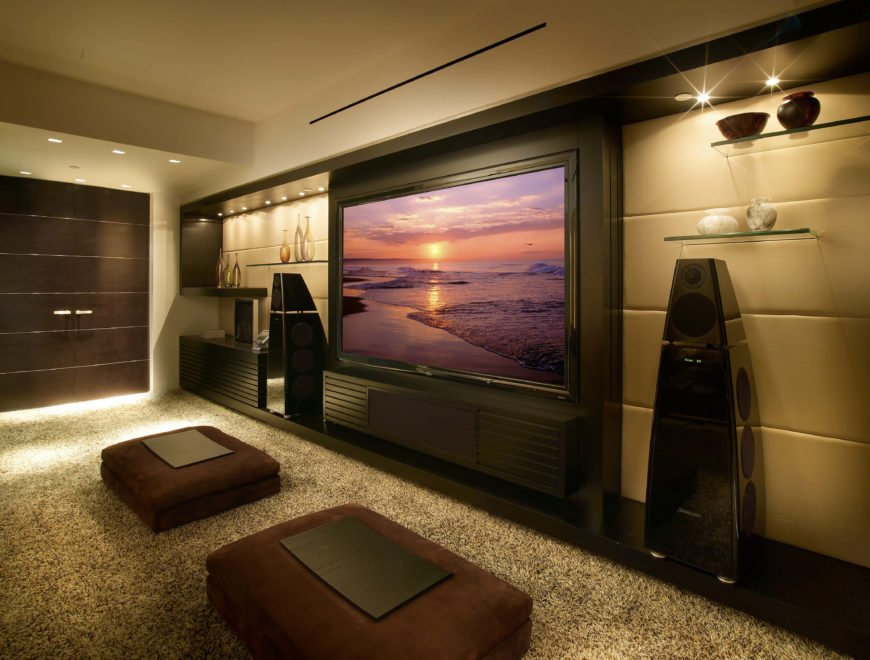 The media room is dominated by the enormous television, with large surround-sound speakers on either side. In front of the television are two velvet ottomans with trays on the top.