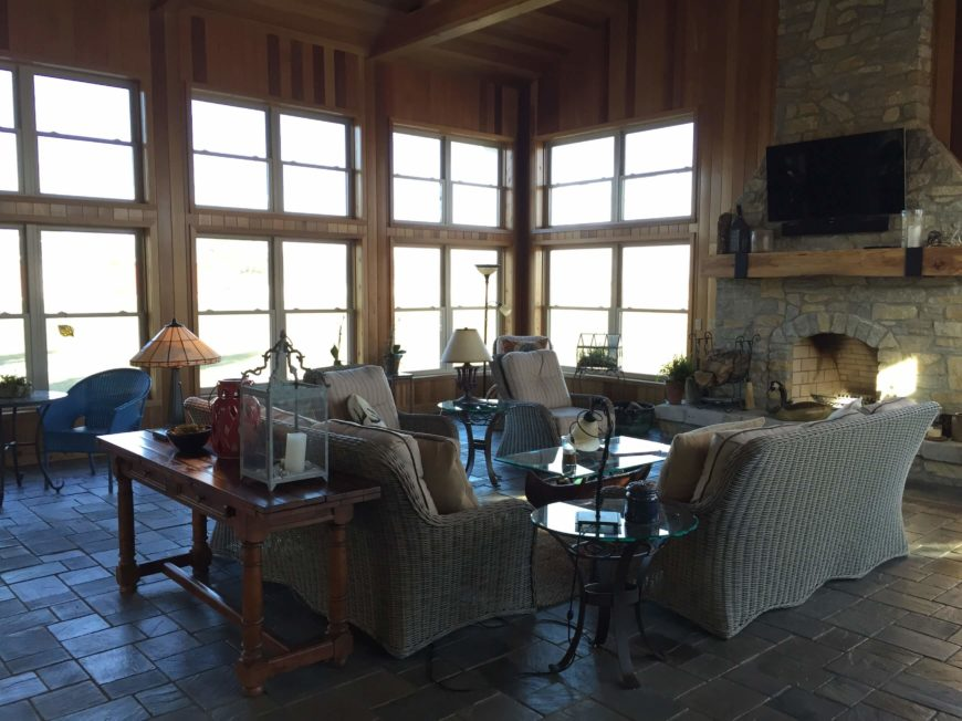 With a wider view, we are able to appreciate the huge array of windows casting sunlight throughout the room. Here we can also glimpse the accent chairs and small table in the left corner, offering additional seating.