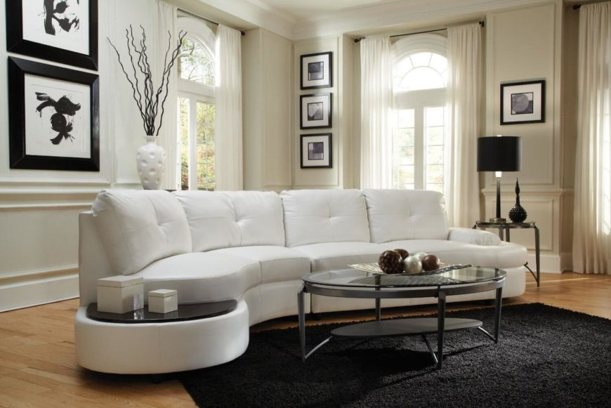 Thick cushioned button tufted white sectional here features rounded edges and a small table-like platform on the left side, a unique touch.