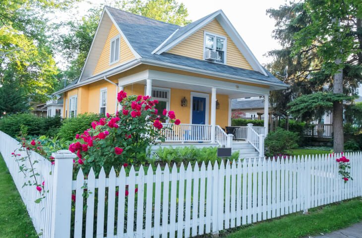 A quaint yellow cottage with a slate roof and a short picket fence surrounding the property. Bright pink roses rail up and down the fence in spots.