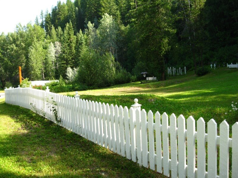 A picket fence serving as a perimeter of a graveyard in the countryside.